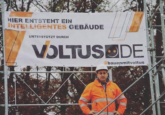 Herr Bellasi mit Bauarbeiterhelm vor dem VOLTUS Banner stehend
