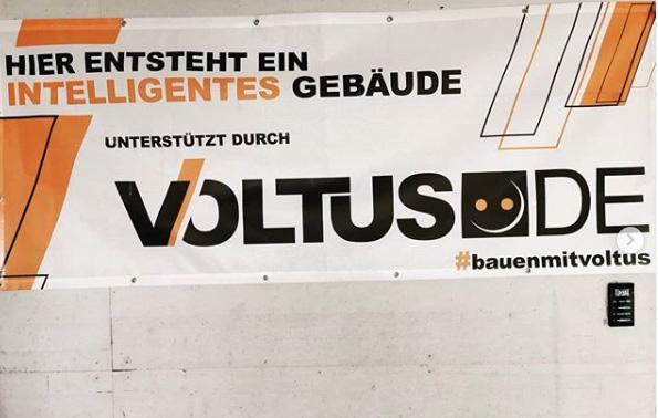 Nahaufnahme des VOLTUS Banners an einer Wand