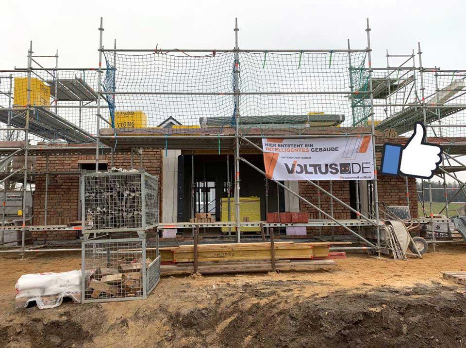 Die Baustelle eines Hauses mit Baugerüst und VOLTUS Banner