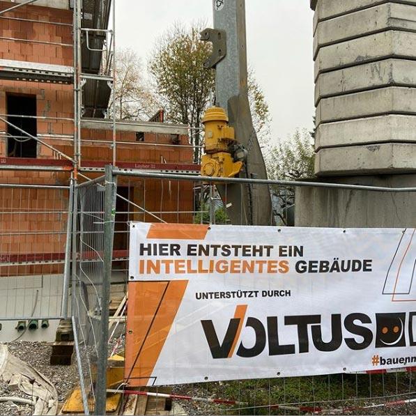 Ein Bauzaun mit VOLTUS Banner und Rohbau eines Hauses