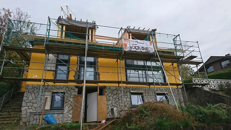 Ein Haus mit Gerüst und VOLTUS Banner