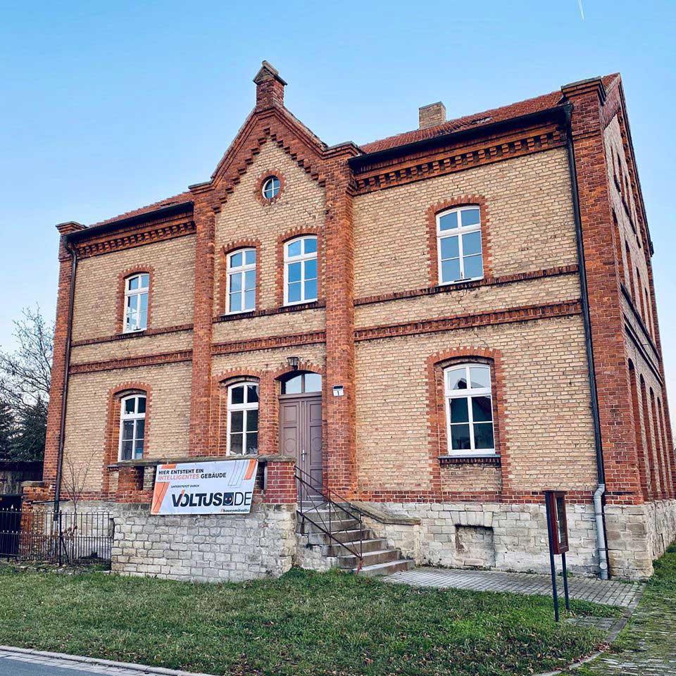 Ansicht eines alten Hauses mit VOLTUS Baustellenbanner