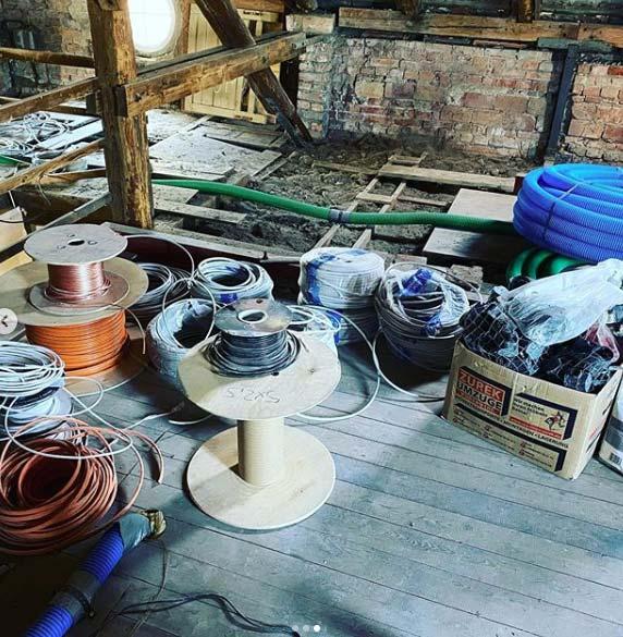 Baustelle eines Hauses mit Kabelrollen und Schläuchen