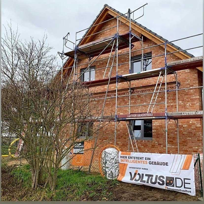 Ein Haus mit Gerüst und VOLTUS Baustellenbanner