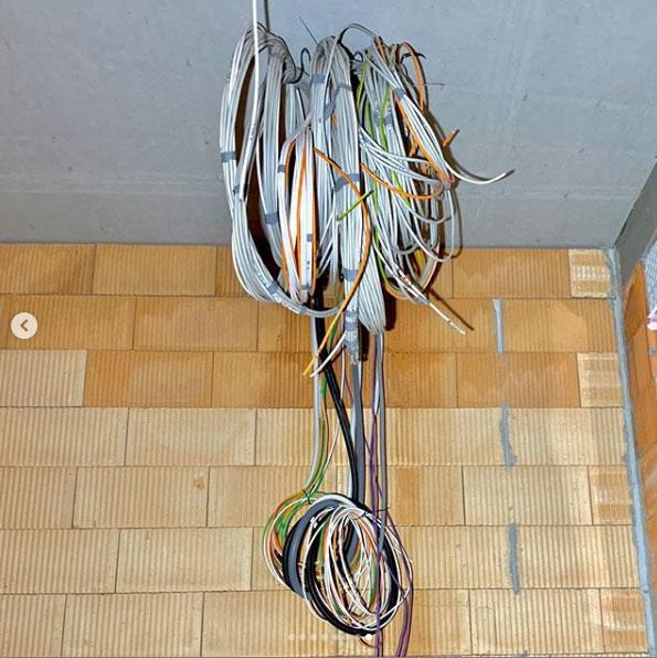 Aufgerollte Kabel von der Decke eines Rohbaus hängend
