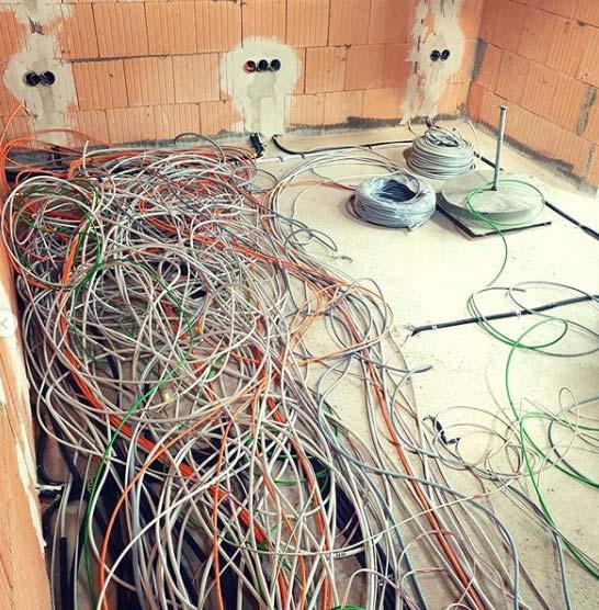 Zu verlegende Kabel durcheinander auf dem Boden eines Rohbaus liegend