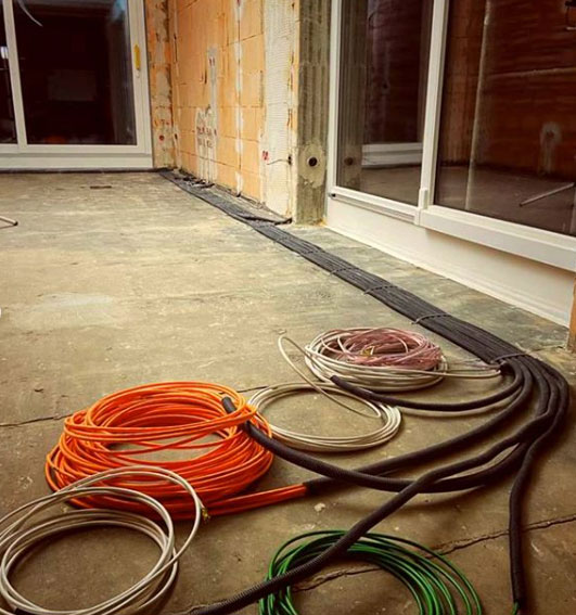 Aufgerollte Kabel auf dem Boden eines Rohbaus liegend