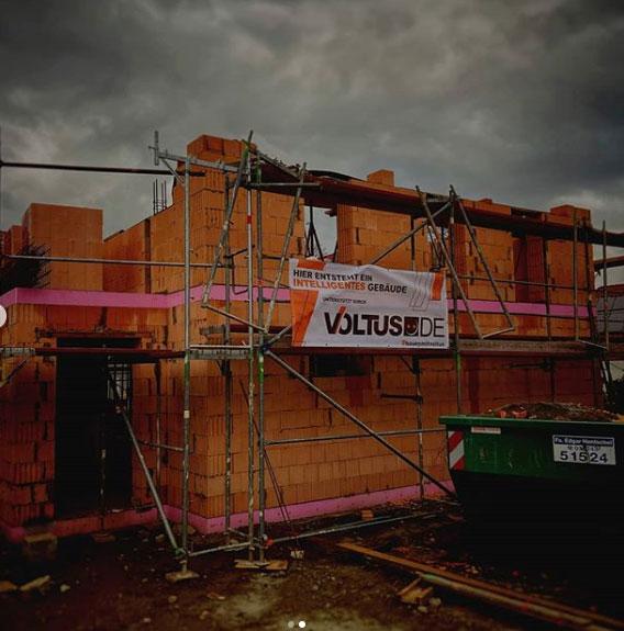 Rohbau eines Hauses mit Baugerüst und VOLTUS Baustellenbanner