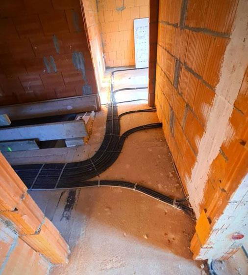 Fußboden eines Innenraums des Rohbaus mit verlegten Kabeln