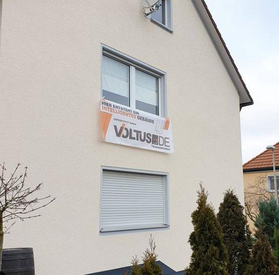 Eine Hauswand mit VOLTUS Baustellenbanner