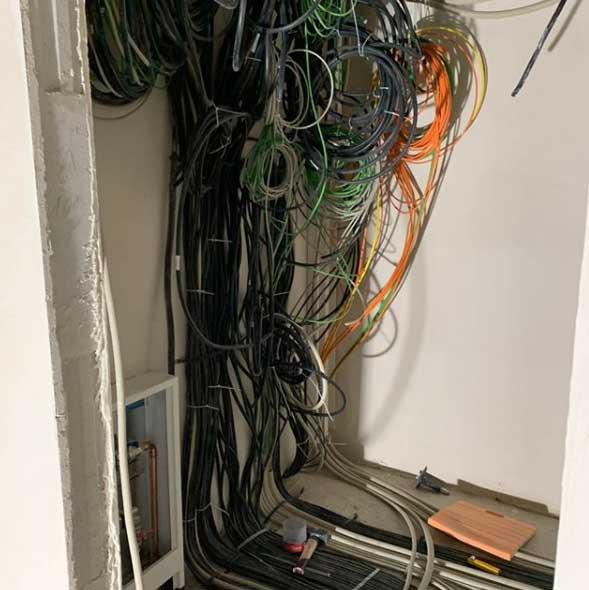 Kabel von der Decke hängend vor einem Verteilerschrank